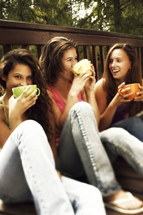 three_relaxed_teen_girls_drinking_coffee_sitting_on_balcony_on_forest_background